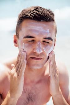 Homem novo que põe o creme tanning em sua face, sunbathing na praia. cuidados de saúde.