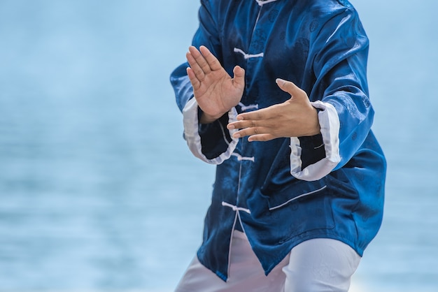 Homem novo que pratica o gongo tradicional de tai chi chuan, de tai ji e de qi, artes marciais chinesas.