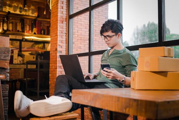Homem novo que senta-se com computador e telefone celular no assoalho de madeira com o pacote que vende o conceito das ideias em linha.