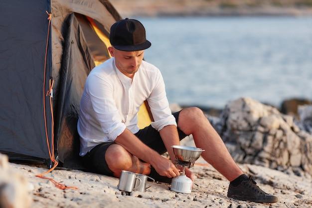 Homem novo que senta-se no litoral rochoso perto da barraca, ajustando a telha do gás.