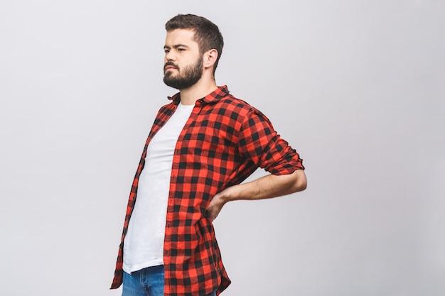 Homem novo que sofre da dor nas costas isolado no fundo branco. conceito de dor nas costas.
