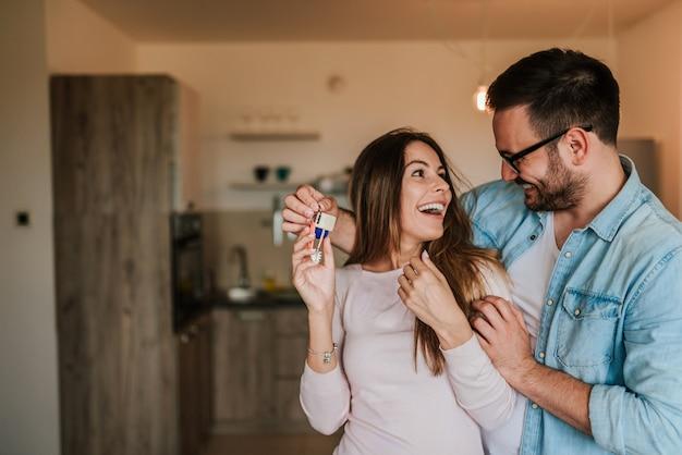 Homem novo que surpreende sua esposa ou uma menina com o apartamento novo.