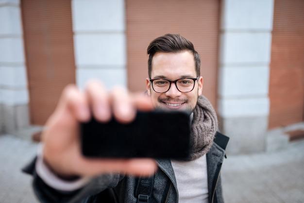 Homem novo que toma o selfie na cidade, close-up.