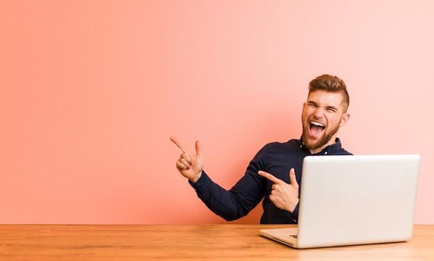 Homem novo que trabalha com seu portátil que aponta com forefingers a um espaço da cópia, expressando o excitamento e o desejo.