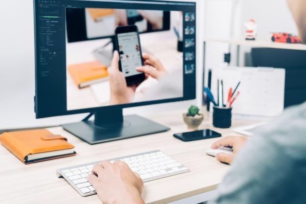 Homem novo que trabalha editando estilos da foto na tela de computador do pc em casa, negócio da fotografia