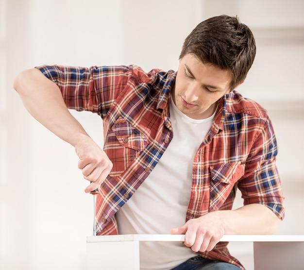 Homem novo que usa ferramentas do reparo para construir a mobília nova.