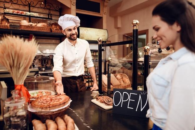 Homem novo que vende o pão ao cliente na padaria.
