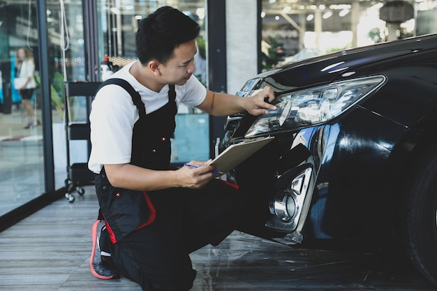 Homem novo que verifica o carro do farol na lista de verificação do caminhão da manutenção preventiva do conceito.