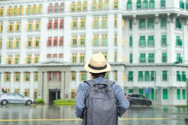 Homem novo que viaja com chapéu, visita asiática de solo do viajante na construção colorida do arco-íris em clarke quay, singapura. marco e popular para atracções turísticas. conceito de viagens na ásia