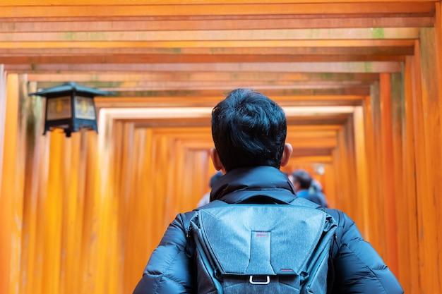 Homem novo que viaja no santuário de fushimi inari taisha, viajante asiático feliz que olha portões alaranjados vibrantes do torii. marco e popular para atrações turísticas em kyoto, japão. conceito de viagens da ásia