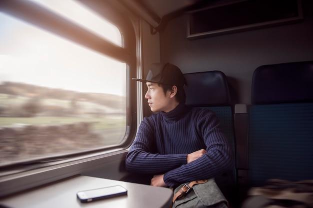Homem novo que viaja olhando para fora a janela ao sentar-se no trem.