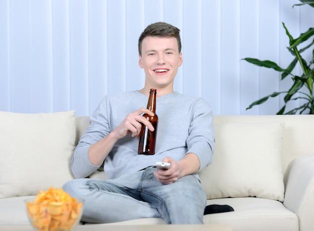 Homem novo relaxado que olha a tevê e que bebe a cerveja.