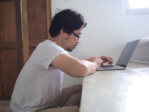 Homem novo relaxado que usa o portátil do computador na cama no quarto.