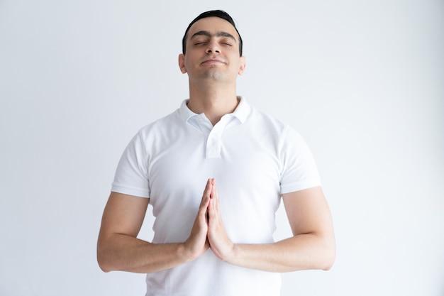 Homem novo satisfeito que reza com seus olhos fechados e que mantém as mãos unidas.