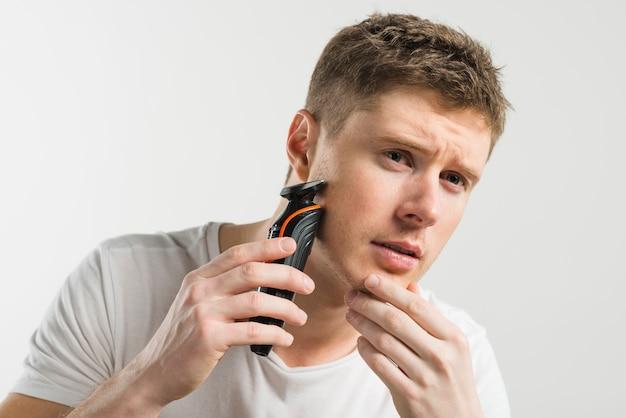 Homem novo sério que barbeia com a máquina contra o fundo branco
