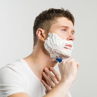 Homem novo sério que barbeia com lâmina azul de encontro ao fundo branco