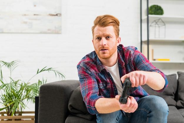 Homem novo sério que joga o jogo video em casa