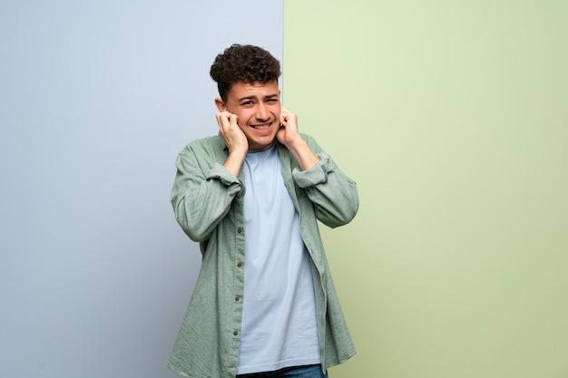 Homem novo sobre as orelhas azuis e verdes da coberta com mãos. expressão frustrada