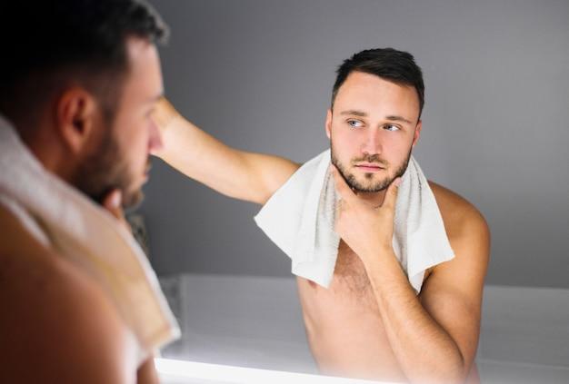 Homem nu com toalha de banho em volta do pescoço