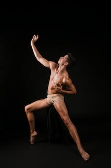 Homem nu, espalhando as pernas e as mãos para os lados