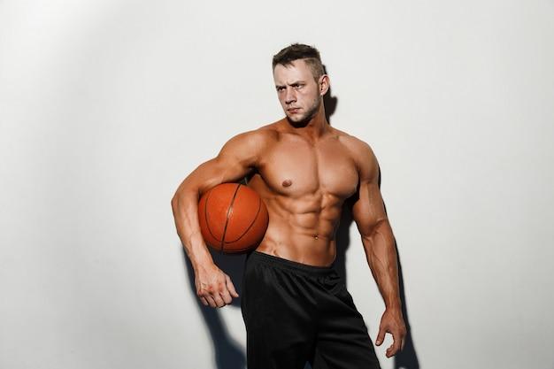 Homem nu muito musculoso segurando uma bola de basquete no estúdio