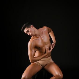 Homem nu na cadeira, dobrando os braços e flexão do tronco.