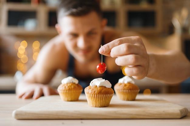 Homem nu no avental cozinhando a sobremesa com cereja na cozinha. homem nu preparando café da manhã em casa, preparação de comida sem roupa