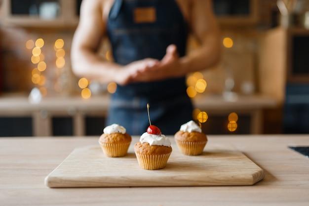 Homem nu no avental cozinhando bolos com cereja na cozinha. homem nu preparando café da manhã em casa, preparação de comida sem roupa