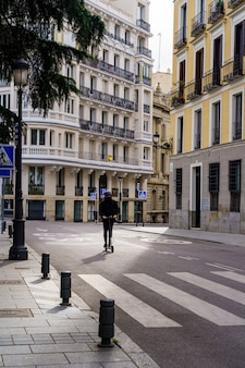 Homem numa scooter elétrica pelas ruas de madrid, sem veículos motorizados, numa manhã de primavera. espanha.