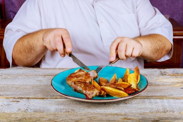Homem, nutritivo, almoço, restaurante, carne porco, bifes, e, batatas