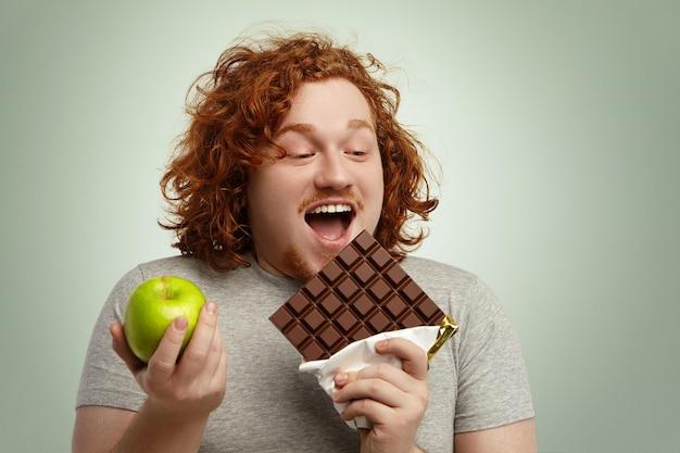 Homem obeso alegre abrindo amplamente a boca, segurando uma grande barra de chocolate em uma mão e maçã verde na outra