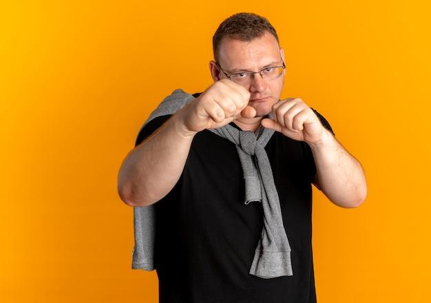 Homem obeso de óculos com camiseta preta posando como um boxeador com os punhos cerrados sobre laranja