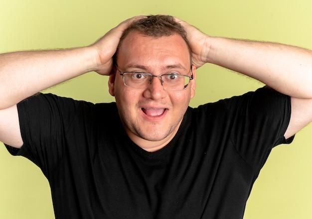 Homem obeso de óculos, vestindo camiseta preta, olhando para a câmera maluco, feliz segurando a cabeça em pé sobre a parede de luz