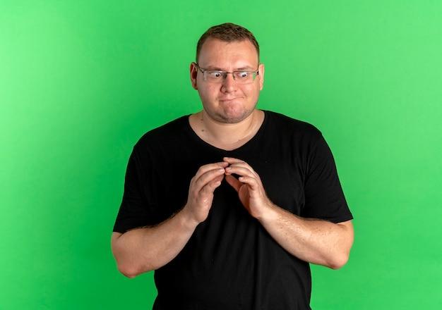 Homem obeso de óculos, vestindo camiseta preta, olhando para o lado com astúcia segurando as palmas das mãos juntas em pé sobre a parede verde