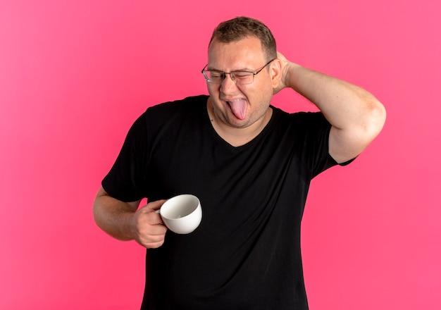 Homem obeso de óculos, vestindo uma camiseta preta, segurando uma xícara de café, se divertindo, esticando a língua e coçando a cabeça em pé sobre a parede rosa