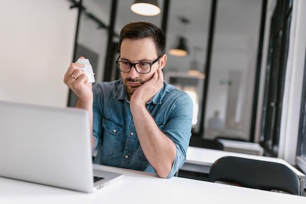 Homem ocasional irritado que trabalha no escritório ao amarrotar o papel e ao olhar o portátil.