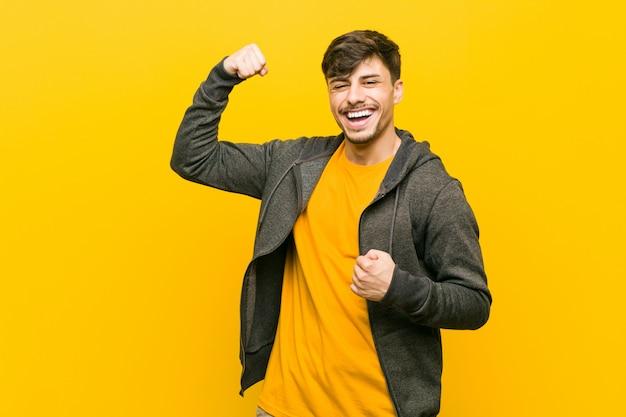 Homem ocasional latino-americano novo que levanta o punho após uma vitória, conceito do vencedor.