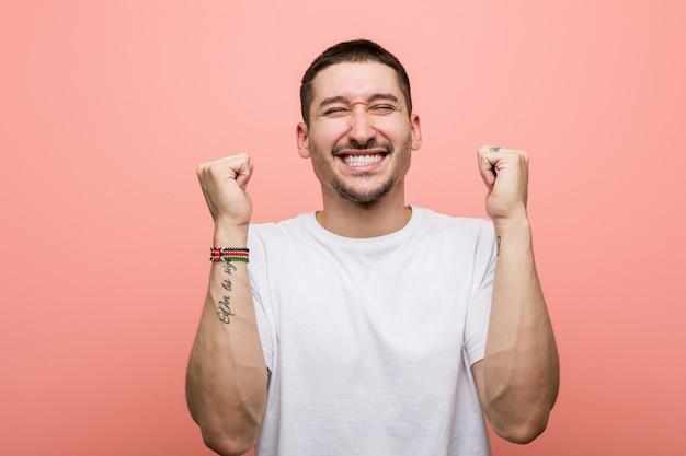 Homem ocasional novo que levanta o punho, sentindo feliz e bem sucedido. conceito de vitória.