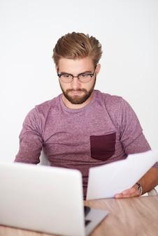 Homem ocupado com laptop e documentos