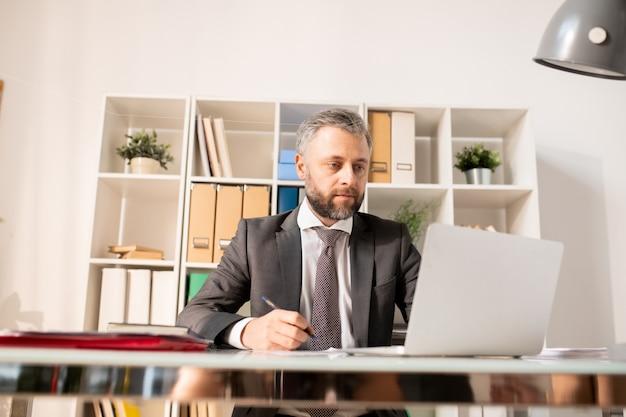 Homem ocupado de fato, analisando informações no laptop