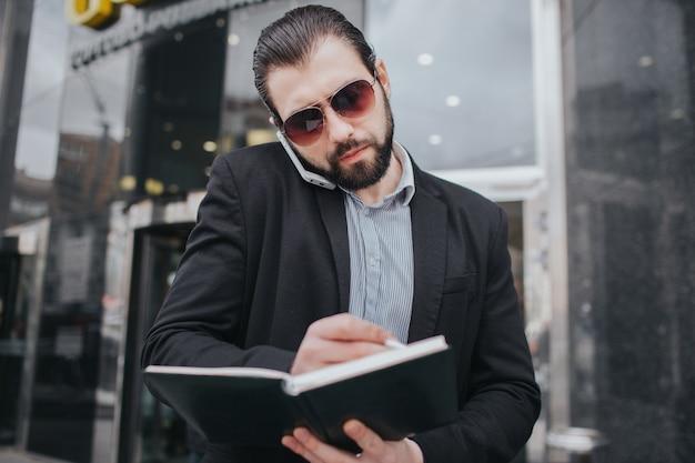 Homem ocupado está com pressa, ele não tem tempo, ele vai falar ao telefone em qualquer lugar. empresário, fazendo várias tarefas. pessoa de negócios multitarefa.
