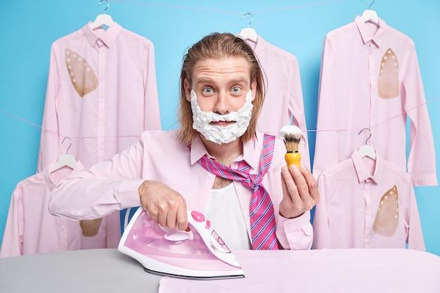 Homem ocupado fazendo a barba e passando roupas lavadas dobradas depois que a lavanderia faz as atividades domésticas cotidianas segura escova usa ferro a vapor elétrico estando com pressa para o trabalho
