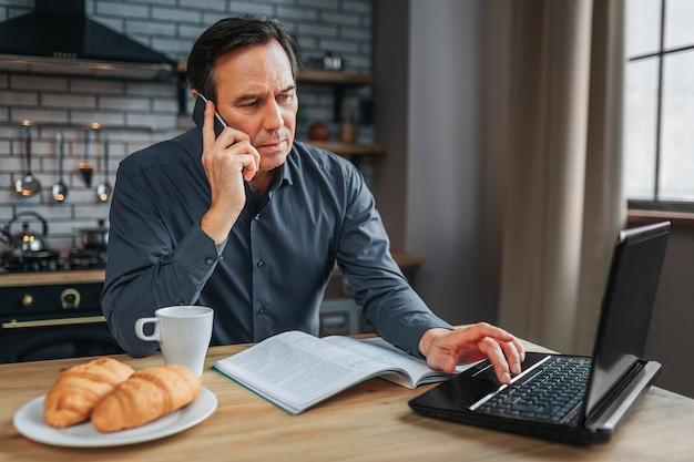 Homem ocupado sentar à mesa na cozinha e falar no telefone. ele digita no teclado do laptop e trabalha. jornal copo branco e prato com croissans na mesa.