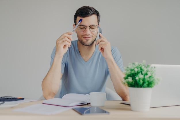 Homem ocupado trabalha em questões organizacionais, fala com parceiro de negócios por telefone celular, mantém os olhos fechados enquanto tenta se lembrar das informações necessárias