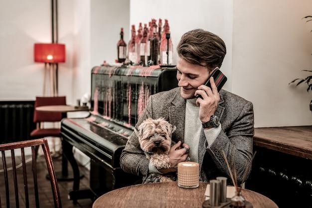 Homem ocupado. um homem com um cachorro esperando por uma reunião importante em um café