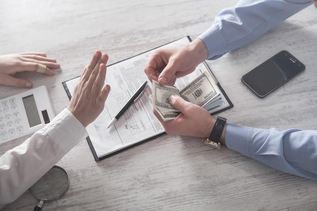 Homem oferece suborno a funcionário no escritório. corrupção, suborno