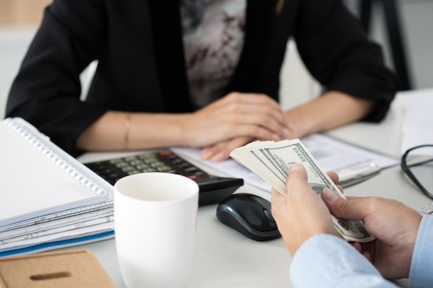 Homem oferecendo lote de notas de cem dólares. fechem as mãos. venalidade, suborno, conceito de corrupção