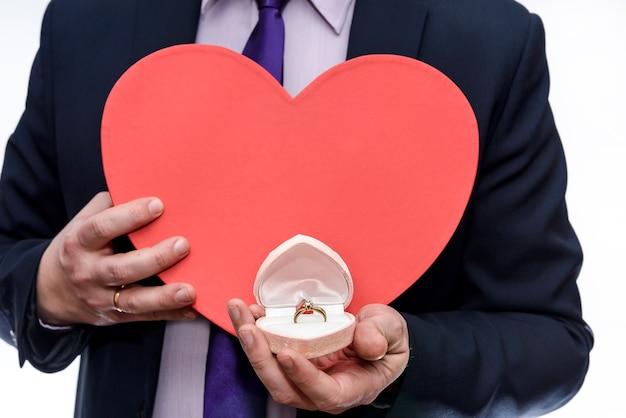Homem oferecendo um anel de ouro e um grande coração vermelho Foto Premium