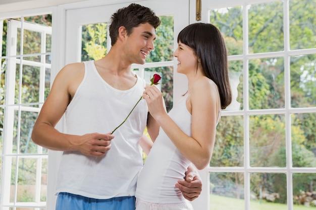 Homem, oferecendo, um, rosa vermelha, para, mulher, em, sala de estar