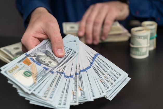 Homem oferecendo um suborno ou pagamento de notas de 100 dólares, segurando um punhado espalhado sobre uma mesa em um conceito de corrupção